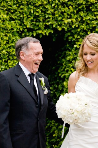 bride-holding-white-bouquet-smiles-as-father-of-bride-laughs