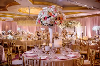 wedding-reception-round-table-tall-centerpiece-white-vase-ivory-hydrangea-pink-coral-rose-gold-chair