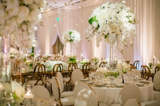 wedding-reception-ballroom-drapery-flowers-hanging-from-ceiling-white-centerpiece-rose-gold-chair
