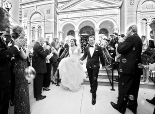 black-and-white-photo-of-newlyweds-exiting-the-church-with-bubbles-blown-at-them