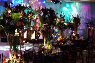 centerpieces-made-with-trees-flowers-and-peacock-feathers