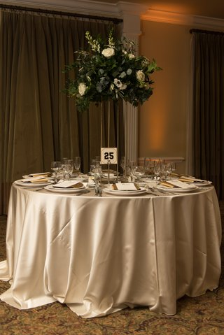 champagne-linens-gold-stand-with-heavy-greenery-centerpiece-table-numbers-from-baseball-players