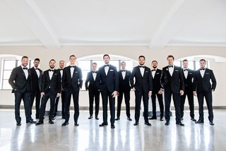 groom-with-groomsmen-in-matching-tuxedos-bow-ties-and-white-pocket-squares-chicago-wedding