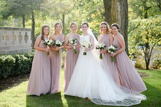 wedding-party-bride-in-classic-bateau-neckline-wedding-dress-bridesmaids-in-one-shoulder-dresses