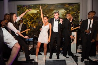 bride-in-a-short-monique-lhuillier-gown-and-groom-in-black-tuxedo-dance-with-the-band