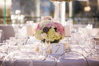 ghost-chairs-around-wedding-reception-table-with-low-centerpiece-succulent-hydrangea-rose-dahlia