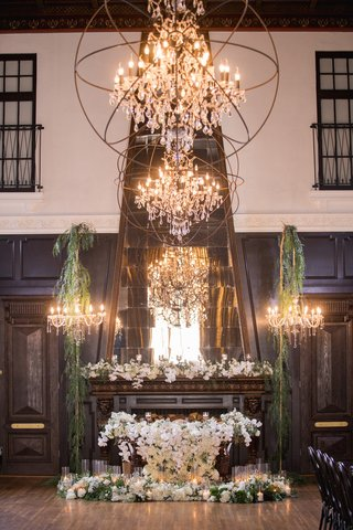 ebell-long-beach-wedding-sweetheart-table-covered-in-orchids-in-front-of-fireplace