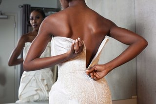 bride-zipping-back-wedding-dress