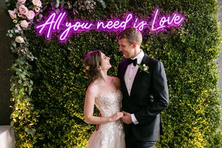bride-and-groom-in-front-of-photo-booth-hedge-wall-neon-pink-purple-all-you-need-is-love-neon-sign