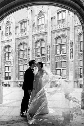 black-and-white-photo-of-bride-in-lace-v-neck-carolina-herrera-groom-in-ralph-lauren-cathedral-veil