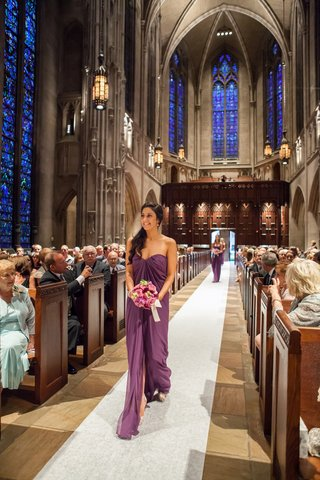 bridesmaid-wearing-strapless-purple-dress-down-aisle