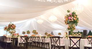 reception-tent-with-white-drapery-and-chandeliers-dark-wooden-chairs-bright-centerpieces
