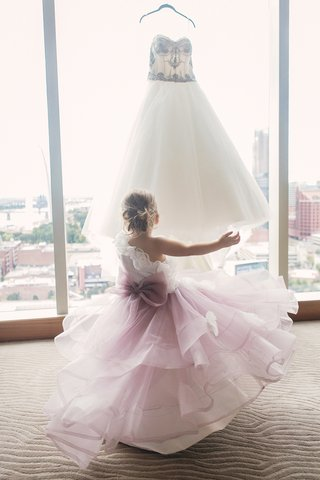flower-girl-in-one-shoulder-dress-with-ombre-purple-skirt-large-bow-ruffles-looking-at-wedding-dress