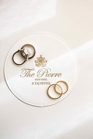 bride-and-grooms-wedding-rings-on-the-pierre-hotel-coaster
