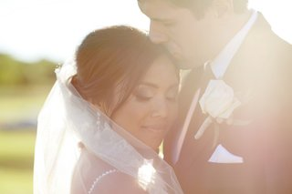 groom-in-a-black-suit-and-tie-kisses-bride-wearing-a-veil-and-dress-with-beaded-straps