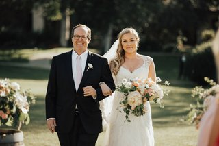 father-of-the-bride-in-black-suite-and-blush-tie-arm-in-arm-with-bride-in-lace-cap-sleeve-gown