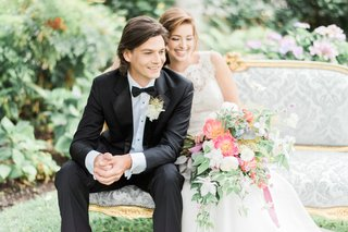 the-bride-and-groom-sit-on-a-victorian-inspired-settee-surrounded-by-bohemian-inspired-flowers