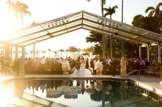 wedding-processional-with-mother-and-bride-pool-with-floating-letter-k-flower-clear-top-tent-sunset