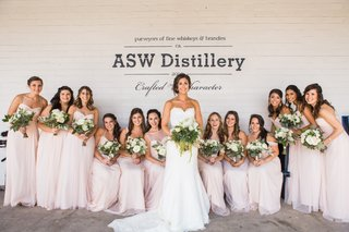bride-and-bridesmaid-hold-bouquets-blush-dresses