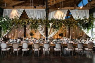 greenery-displayed-above-kings-table-at-wedding-reception-drapery