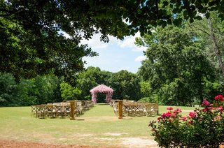 wedding-ceremony-on-grass-lawn-pink-chuppah-white-flowers-vineyard-chairs-wood-and-grass-aisle