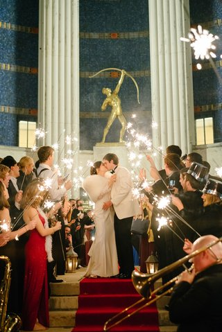 bride-in-fur-stole-wrap-kissing-groom-in-white-tuxedo-jacket-sparkler-exit-red-carpet-hall-of-state