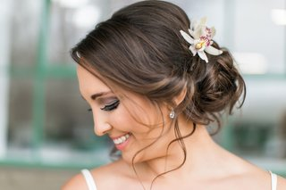 brunette-bride-with-low-bun-and-soft-tendrils-orchids-in-hair
