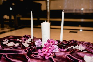 unity-candle-with-inscription-on-table-with-purple-linens-and-flower-petals-church-ceremony-baptist