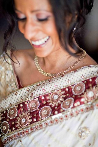 bride-in-a-white-sari-with-burgundy-and-gold-embroidery-accessorizes-with-gold-earrings-and-necklace