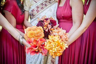bridesmaids-hold-bouquets-of-yellow-and-orange-flowers