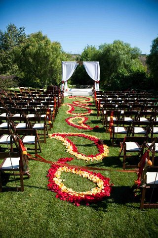outdoor-wedding-aisle-decorated-with-a-red-and-yellow-paisley-pattern