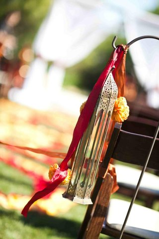 a-lantern-red-and-orange-ribbons-with-yellow-flowers-suspended-on-a-hook-for-an-outdoor-wedding