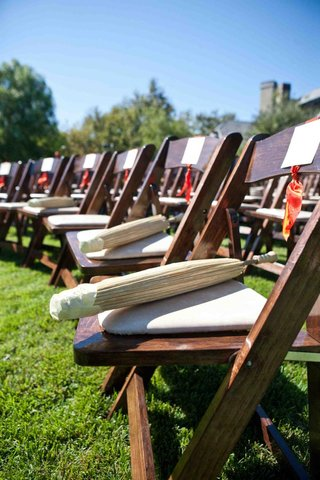 paper-parasols-are-set-on-chairs-for-an-outdoor-wedding