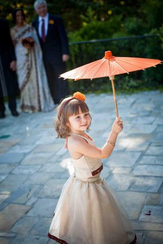 flower-girl-in-an-ivory-two-piece-outfit-with-burgundy-and-gold-trim-holds-an-orange-parasol