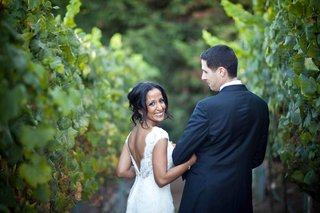 bride-in-a-cap-sleeve-lace-gown-walks-among-vineyard-with-groom-in-a-dark-suit