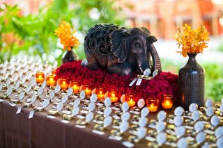 wedding-place-card-table-decorated-with-an-elephant-on-a-bed-of-red-flowers-surrounded-by-candles