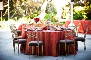 wedding-reception-table-with-red-tablecloth-and-golden-chiavari-chairs-with-plum-cushions