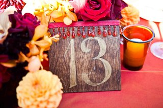 wedding-reception-table-number-on-a-wood-board-decorated-with-red-ribbon-and-beads
