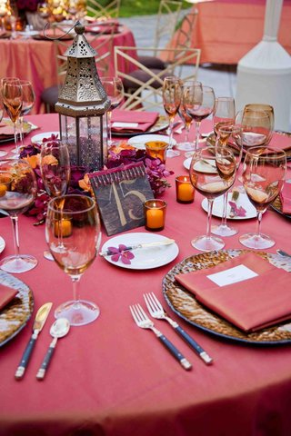 wedding-reception-table-with-red-tablecloth-and-napkin-amber-glassware-and-earth-toned-chargers