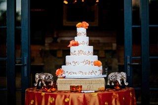 white-wedding-cake-with-golden-swirls-and-fresh-orange-flowers