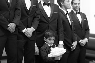 black-and-white-photo-of-young-ring-bearer-in-tux-standing-in-front-of-groomsmen