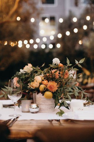 outdoor-wedding-reception-bistro-lights-small-centerpiece-kumquats-fresh-fruit-orange-dahlia-greens