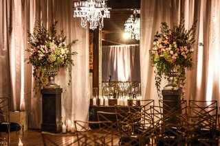 blush-burgundy-green-floral-arrangement-on-stand-with-crystal-chandelier-at-ceremony