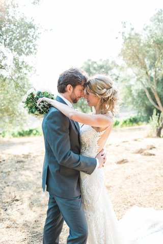 bride-closes-eyes-and-puts-arms-around-groom-while-holding-bouquet-berta-wedding-dress-grey-suit