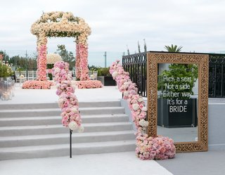 stairs-up-to-ceremony-arbor-with-gold-frame-mirror-pick-a-seat-not-a-side-same-sex-wedding