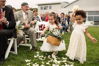 flower-girls-tossing-white-flower-petals-short-sleeve-dresses-grass-aisle-outdoor-wedding