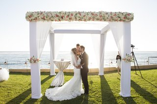bride-in-wedding-dress-and-groom-in-tuxedo-kiss-at-oceanfront-wedding-ceremony-in-mexico