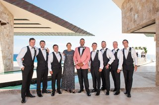groom-in-salmon-tuxedo-jacket-groomsmen-in-suit-vests-groomswoman-in-black-grey-sequin-gown