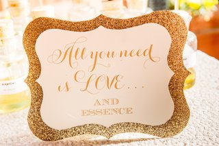 wedding-shower-perfume-station-with-a-gold-glitter-sign-all-you-need-is-love-and-essence