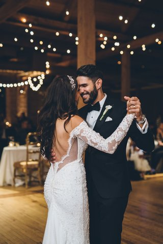 bride-and-groom-first-dance-rustic-wedding-twinkle-lights-lace-long-sleeves-low-back-ruching-tuxedo
